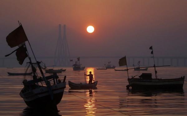 A fisherman steers his boat toward the shore near the Bandra-Worli sea link bridge as the sun sets in Mumbai on Jan. 24, 2013.