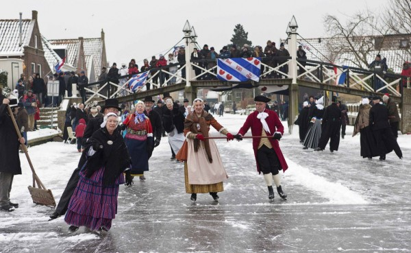Skaters dressed in traditional Dutch costumes skate on the canal in Hindeloopen on Jan. 26, 2013. When the canals and lakes freeze, the Dutch get out their skates and venture out on the ice. In Friesland, skaters dressed in traditional costumes gather for a day of ice skating, pole-sledding, and other entertainment on ice. The skaters wear an old-fashioned form of skate with special blades to help them glide across the ice without tiring, and usually skate together in couples or groups.