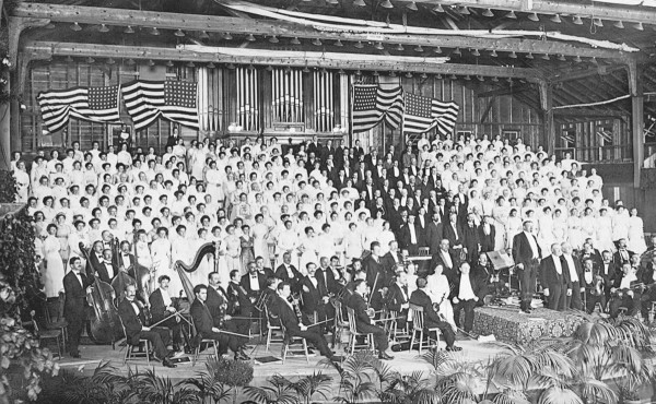 William Rogers Chapman is front and center in the tuxedo. Judging by the 48-star flag, this isn't earlier than 1912, and is probably around 1920.