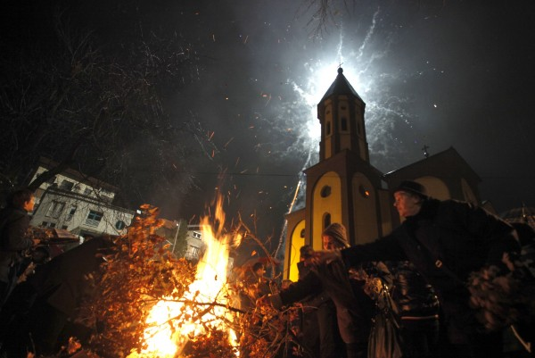 Burning Yule logs and fireworks are seen in front of a church during the eve of the Orthodox Christmas, in the central Bosnian town of Zenica January 6, 2013. Orthodox Christians mark Christmas according to the Julian calendar on January 7.