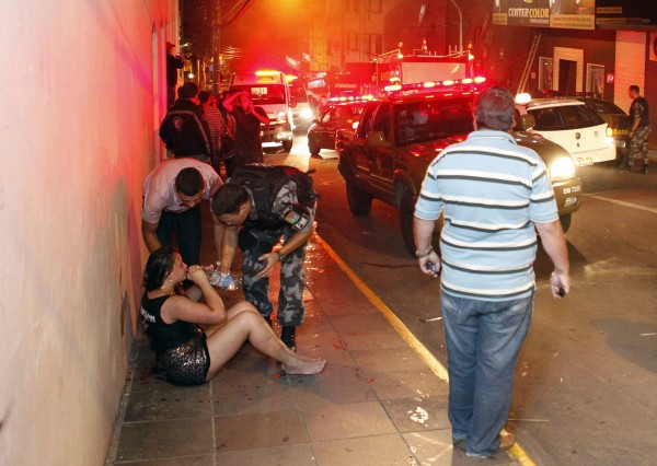 A police officer helps a woman next to Kiss nightclub in the southern city of Santa Maria, 187 miles west of the state capital of Porto Alegre, in this picture taken by Agencia RBS, January 27, 2013.
