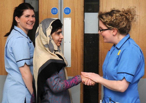 Pakistani schoolgirl and education activist Malala Yousufzai (center) smiles with nurses as she is discharged from The Queen Elizabeth Hospital in Birmingham, England, in this handout photograph released on Jan, 4, 2013. The Pakistani girl shot in the head by the Taliban for advocating girls' education has been discharged from a specialist British hospital after doctors said she was well enough to spend some time recovering with her family.
