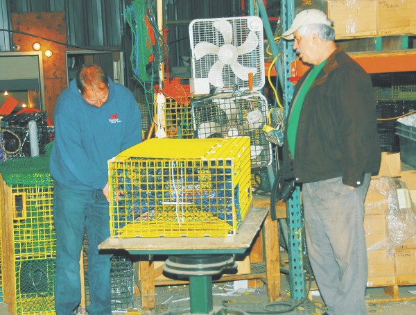 Stephen Brooks demonstrates a lobster trap to a customer.