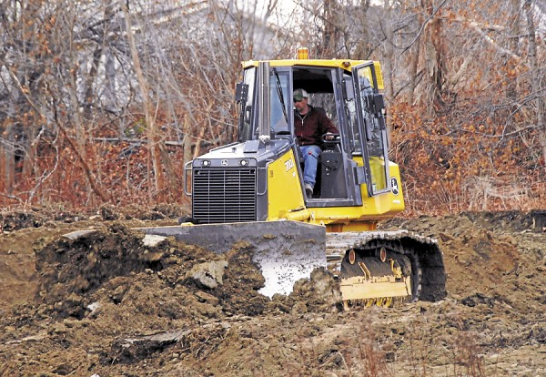 A Bangor Public Works Department equipment operator drives a John Deere bulldozer while leveling an open area behind the former Bangor Armory in early December. The project also involved the Bangor Parks and Recreation Department, which is building an outdoor play area behind the armory.