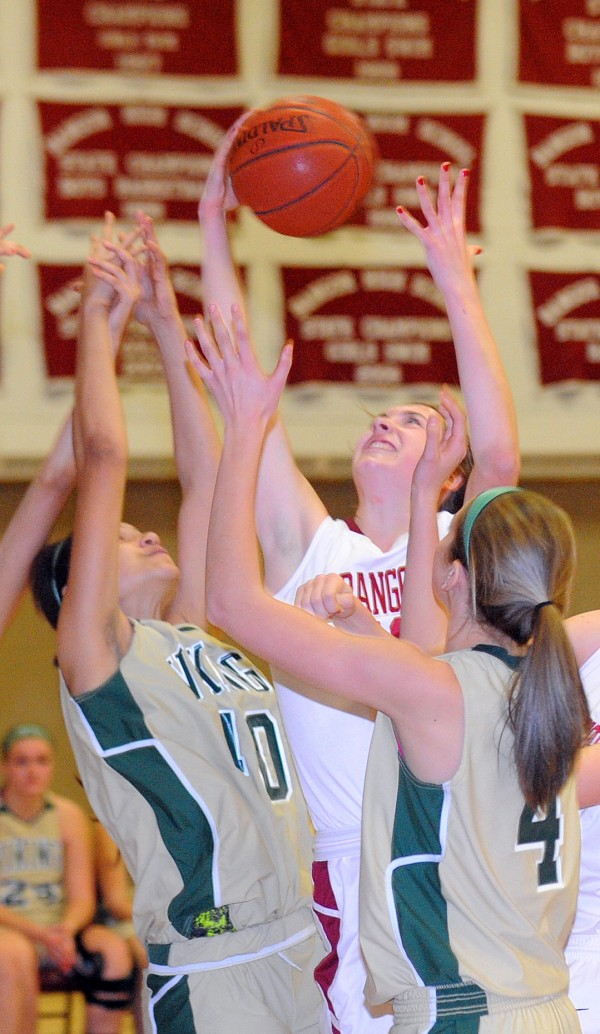 Bangor High School's Cordelia Stewart (center) takes a rebound over Oxford Hills High School players Tianna Sugars (left) and Anna Winslow (right) during the game in Bangor Monday.