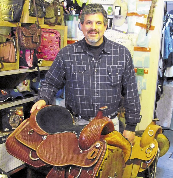 Owner Barry Gass exhibits one of the many saddles available at Gass Horse Supply.