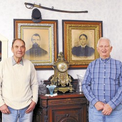 First cousins Robert Modery (left) and John A. Modery stand in the living room of Robert's Orono home. Displayed behind them are portraits of their Civil War-era great-grandparents, Pvt. John H. Modery and his wife, Anna. On the wall above the portraits hang a Union kepi and a sword that Private Modery had when he served in Co. H, 1st Maine Heavy Artillery.