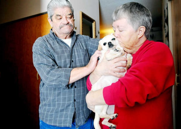 Richard and Kitty Roy give Lady attention at their Lewiston apartment. Lady was born eight months ago with deformed front legs.