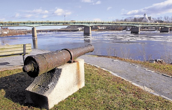 From the Bangor shore, a corroded cannon lost in the Penobscot River in 1779 points toward the Joshua Chamberlain Bridge and Brewer shore (right). The light green paint that covers the bridge has flaked away in many places, exposing the underlying steel to corrosion. In a project set to begin this spring, a contractor hired by the Maine Department of Transportation will remove the bridge's existing lead-based paint and cover the steel with a primer and two coats of a non-lead-based paint. During the project, traffic will be restricted to one lane, with vehicles traveling only from Brewer to Bangor.