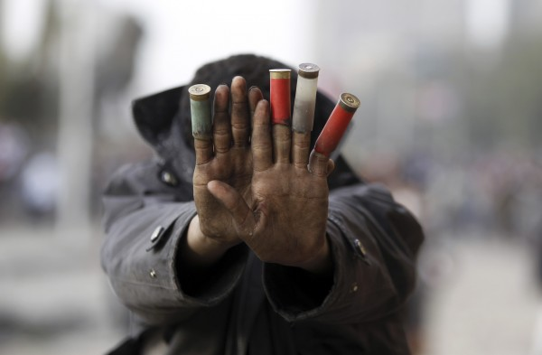 A protester against Egypt's President Mohamed Mursi shows expended shotgun cartridges that he said was fired by riot police during clashes along Qasr Al Nil bridge, which leads to Tahrir Square in Cairo Jan. 27, 2013. Egyptian President Mohamed Mursi announced on Sunday he was imposing a state of emergency for 30 days in three cities along the Suez Canal that have been the scene of the worst violence that flared at the weekend, killing more than 45 people.