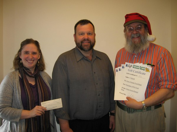 Local business owners Debra Bell (left) and Don Hanson (right) present checks to Rob Crone, director of nutrition at the Eastern Area Agency on Aging. Bell and Hanson collaborated on a joint pet-photo shoot that helped raise money for EAAA's Furry Friends Food Bank.
