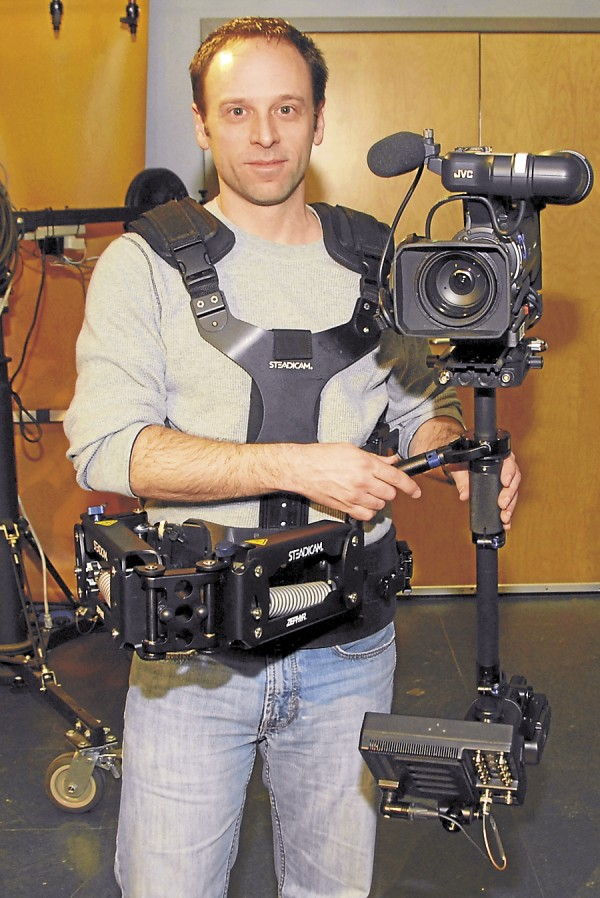 Todd Eastman wears the full Steadicam gear that a camera operator would utilize during actual filming. The vest provides a mount for the hinged arm (foreground) that holds the rig on which the actual camera and battery are mounted.