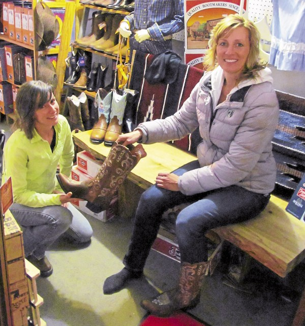 Jillian Marcho (left) helps customer Heather Dorr of Milbridge select boots at Gass Horse Supply.