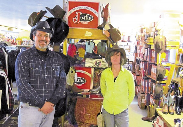 Owner Barry Gass and employee Jillian Marcho show off some of the Western wear available to Gass Horse Supply in Orono.