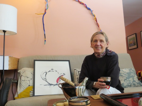 Gail Page sips from a real teapot in front of one of her teapot paintings. The teapot, she says, carries such warm feelings of companionship and comfort that it continues to find its way into much of her artwork.