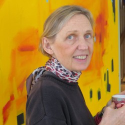 """Gail Page, holding a cup of tea, stands in front of a large canvas she painted with one of her favorite """"positive energy colors."""""""