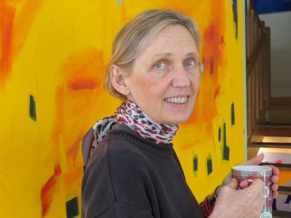 Gail Page, holding a cup of tea, stands in front of a large canvas she painted with one of her favorite &quotpositive energy colors.&quot