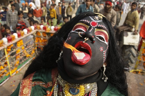 A man dressed as Hindu goddess Kali, the goddess of power, performs with a burning camphor tablet on his tongue during a religious procession ahead of the &quotKumbh Mela&quot, or Pitcher Festival, in the northern Indian city of Allahabad January 6, 2013. During the festival, hundreds of thousands of Hindus take part in a religious gathering at the banks of the river Ganges. The festival is held every 12 years in different Indian cities.