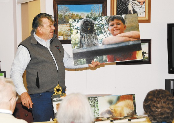 John Ford shows a photo of his son and one of the two owls he raised to the crowd at Sunbury Village Independent Living Community in Bangor last week. Ford is promoting his bestselling book, &quotSuddenly, the Cider Didn't Taste So Good,&quot containing memorable, and often humorous, anecdotes of his time as a Maine game warden.