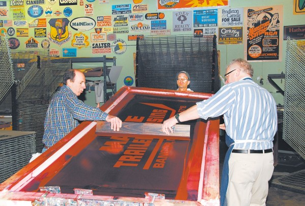 "David Farrar (left) and Tim McLeod (right) apply paint during the screenprinting process while Leonard ""Pat"" Partridge assists. Note the wall, which is covered with print jobs from years past, as most of the walls in the facility are."