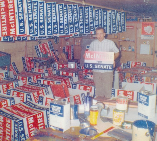 In this 1964 photo, employee Dick Lynch stands with stacked and drying campaign signs.