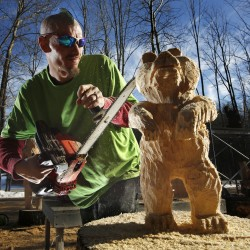Josh Turner uses the tip of his chain saw to add detail to a bear sculpted from a pine log Monday, Jan. 14, 2013, in Topsham.