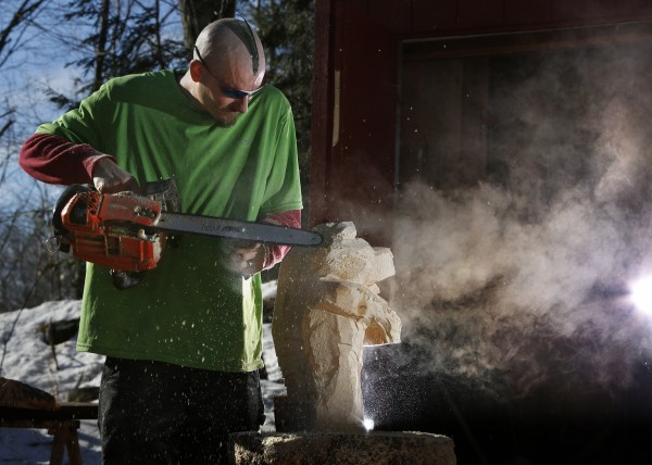 Thirty minutes after he started, a bear emerges from a cloud of sawdust from Josh Turner's chain saw on Monday, Jan. 14, 2013, in Topsham.
