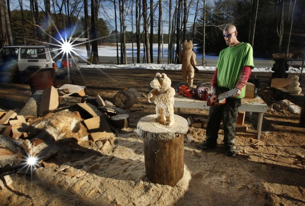 Chain saw artist Josh Turner steps back to examine his work while sculpting a bear on Monday, Jan. 14, 2013. Turner creates his art in a lot at the intersection of Route 201 and Bradley Pond Road in Topsham.