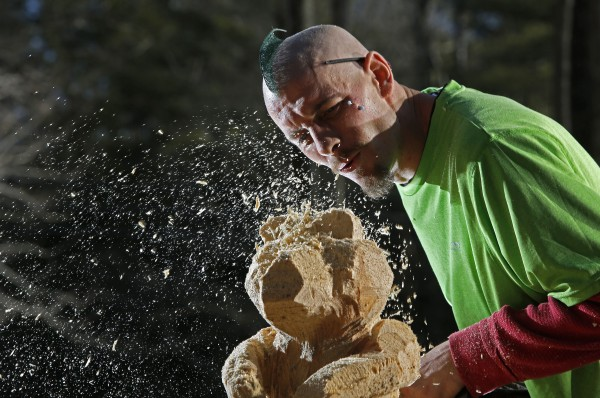 Josh Turner blows sawdust from a bear he sculpted with a chain saw on Monday, Jan. 14, 2013, in Topsham.