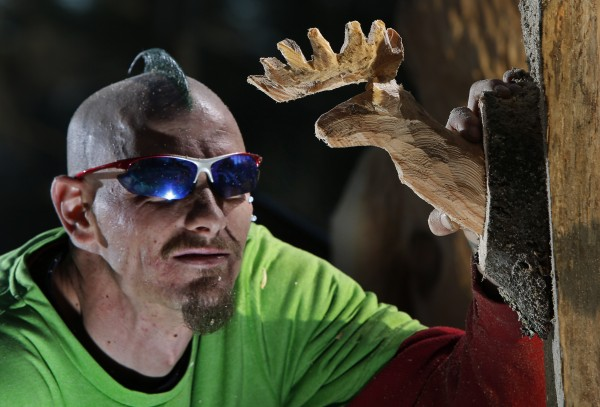 Josh Turner examines a miniature deer head he carved, on Monday, Jan. 14, 2013, in Topsham. It is the smallest carving he's made in his four-year career as a professional chain saw artist.