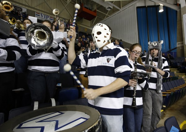 Sixth-year student Mike Knee, of Bow, N.H., wheres a goalie mask while playing bass drum in the U Maine band during a hockey game against Mercyhurst at the Cumberland County Civic Center, Friday, Jan. 4, 2013, in Portland, Maine