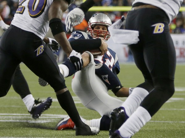New England Patriots quarterback Tom Brady (12) slides down to the turf after running in the first half against the Baltimore Ravens during the NFL AFC Championship football game in Foxborough, Mass., Jan. 20, 2013.