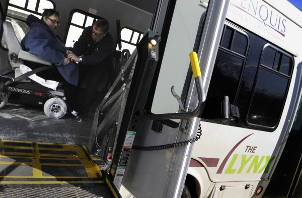 Penquis Lynx bus driver Ronald Cote buckles Sandra Rocco of Bangor and her wheelchair in place after she used a chair lift to board the bus for her departure from Penquis in Bangor Tuesday, Feb. 21, 2012. Officials had previously announced the state's first expansion of American Disabilities Act services for the Federal Transit Association's New Freedom Program.