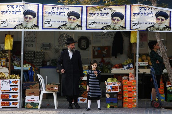 An ultra-Orthodox Jewish man stands beneath campaign posters depicting Rabbi Ovadia Yosef, the spiritual leader of the ultra-Orthodox Shas party, in the southern city of Ashdod, Israel, on Thursday, Jan. 17, 2013. A fixture in successive governments, Shas, the ultra-Orthodox party draws its support from the fast-growing community of religious Jews of Middle Eastern origin whose spiritual leader is the 92-year-old, Iraqi-born rabbi Ovadia Yosef. According to opinion polls, it will maintain its 11 seats in parliament.
