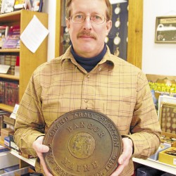 "Paul Zebiak, the owner of Maritime International in downtown Bangor, displays the ""Grand Army Glutton"" medal won by Frederick Stackpole of Kenduskeag on Jan. 23, 1879. The steel-alloy medal is 6 inches in diameter and weighs 95.04 ounces."