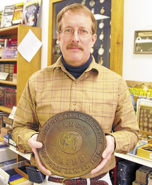 Paul Zebiak, the owner of Maritime International in downtown Bangor, displays the &quotGrand Army Glutton&quot medal won by Frederick Stackpole of Kenduskeag on Jan. 23, 1879. The steel-alloy medal is 6 inches in diameter and weighs 95.04 ounces.