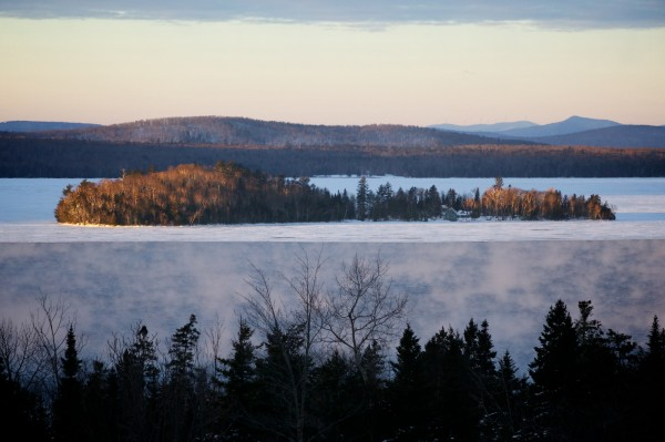Open water steams at sunrise on Rangeley Lake just before members of the Maine Warden Service resume their search for three missing snowmobilers Thursday, Jan. 3, 2013.