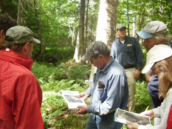 Lands committee members look on as Jim R. Robbins reviews a map of the property, with Jim A. Robbins in the background