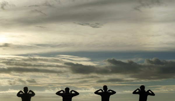 A group of men perform physical exercise training during sunset at Galle Face green in Colombo on Jan. 9, 2013.