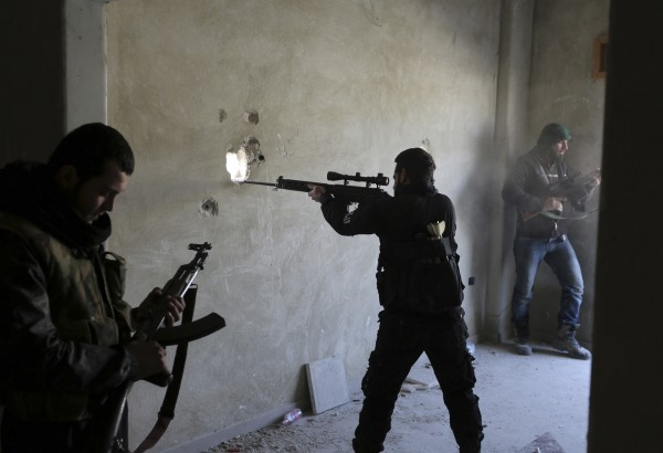 A fighter from the Free Syrian Army's Tahrir al Sham brigade aims his rifle in Mleha suburb of Damascus Jan. 27, 2013.