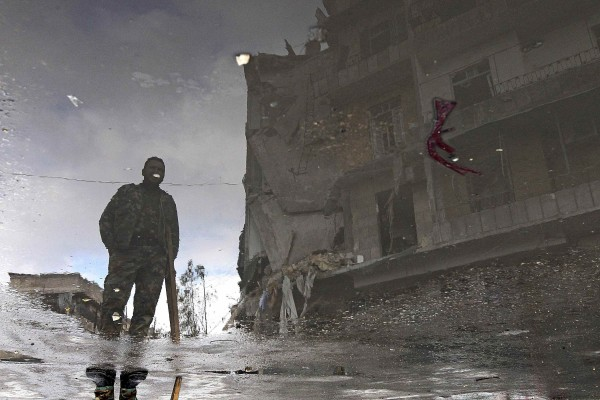 A Free Syrian Army fighter is reflected in a puddle of water as he stands near a damaged building in Aleppo January 6, 2013.