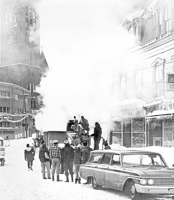The Bangor Public Works Department sought assistance in any form to cope with the aftermath of the Dec. 30, 1962 blizzard that dumped 25.5 inches of snow on the Queen City. A state-of-the-art snow melter transported north from Portland was set up on New Year's Day 1963 near the intersection of Central, Hammond, Main, and State streets in downtown Bangor to melt snow blocking parking spaces in the area. In the background is the tower of Bangor City Hall, which then stood at Columbia and Hammond streets.