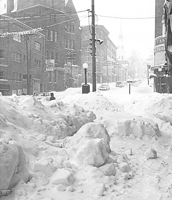 Snow banks clogged the intersection of Central Street (sign outside the W.T. Grant Co. store) and Hammond Street (center) as a few adventurous motorists navigated Bangor streets on Jan. 1, 1963. Two days earlier, a prediction of snow flurries had exploded into a historic blizzard that dumped 25.5 inches of snow on the lower Penobscot Valley. The steeple of the Hammond Street Congregational Church is visible in the distance.
