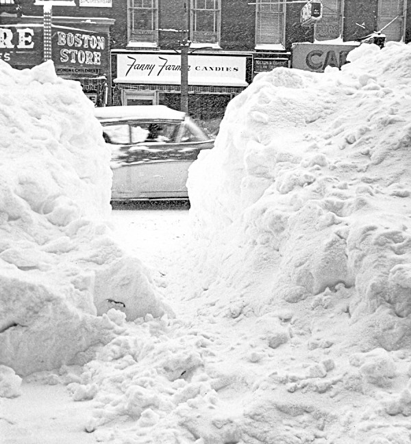 A car whizzes past as BDN photography Danny Maher photographs an opening in the massive snowbank lining Main Street in downtown Bangor on Jan. 1, 1963. Across the way are the Boston Store and Fanny Farmer Candies.