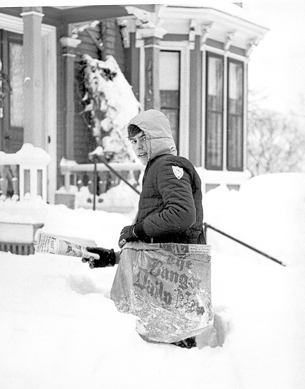 An unidentified BDN newspaper carrier delivers an early January 1963 edition of the NEWS to a snowbound house in Bangor. A blizzard had just dumped 25.5 inches of snow on the Queen City.