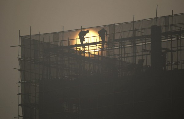 Laborers install scaffolding at a residential building construction site during sunrise on a hazy day in Zhengzhou, Henan province Jan. 14, 2013. China may postpone expanding a trial property tax nationwide, a senior tax official said in remarks published on Monday.