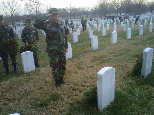 Cadet Airman First Class Nicholas Tinto salutes after placing a wreath at a grave in Arlington Cemetery. Higgins photo