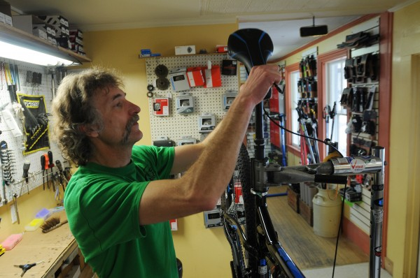 Jim Rose, owner of Rose Bike shop in Orono, fits a bike with a seat on Tuesday. Rose says he's disappointed in Lance Armstrong but thinks Armstrong has done a lot of good for people and should be credited for that.
