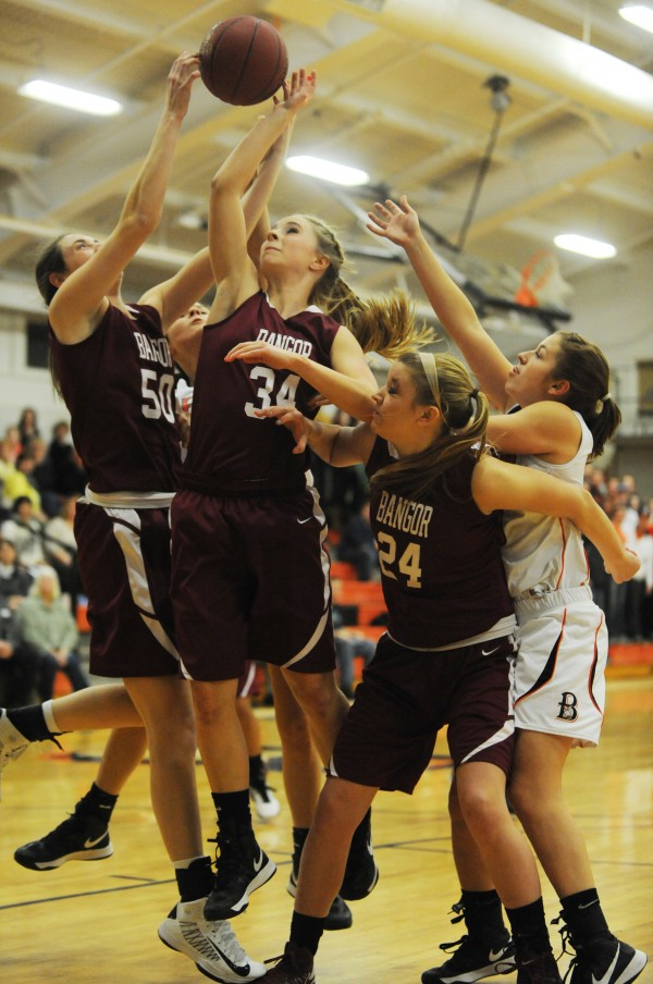Bangor's Cordelia Stewart, Sarah Bragg and Rachel Taft along with Brewer's Alexa Grindle all vie for a rebound during first half action at Brewer on Monday.