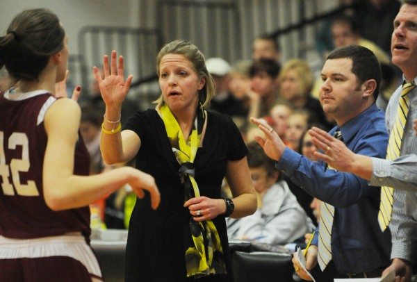 Bangor's head basketball coach Katie Herbine and her staff give Mary Butler high-fives as she comes off the court on Monday against Brewer.